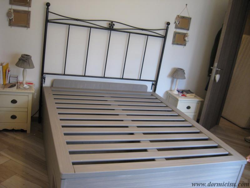 panoramica del letto con testata in ferro battuto.