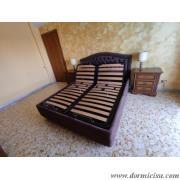 panoramica del letto con gli schienali della rete alzati.
